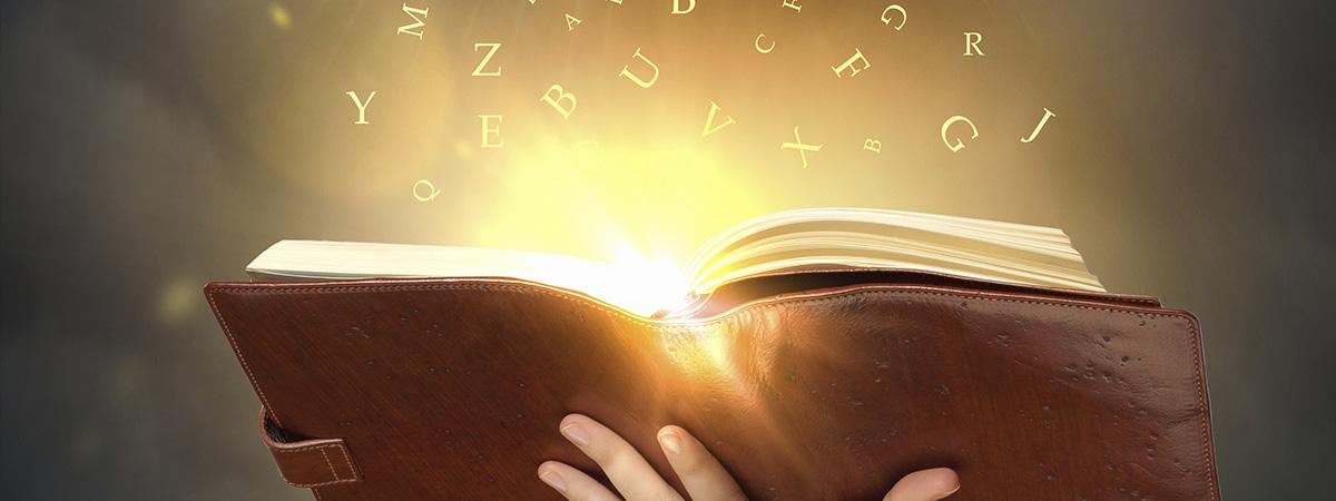 livre ouvert avec lumière jaune et lettres