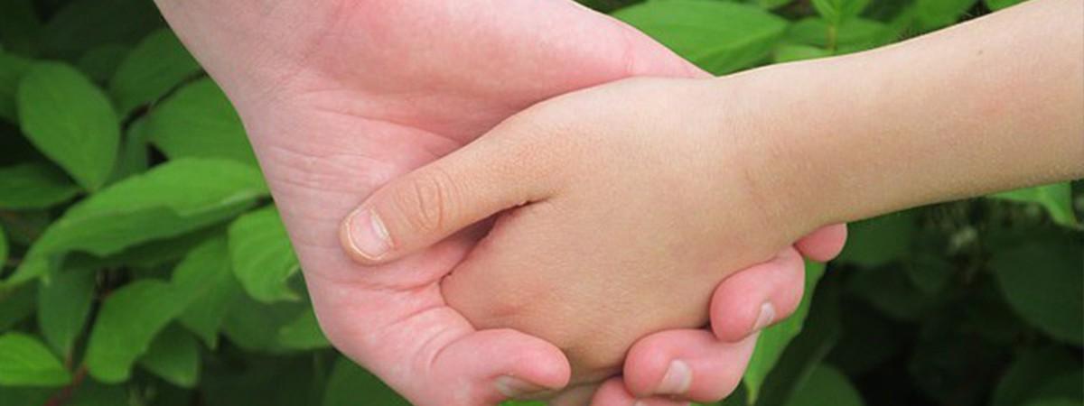 main dans la main avec feuilles vertes en fond